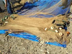 The home-made net is checked for sticks and debris and then laid out to dry.